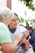 Seniorin und Pflegerin sitzen zusammen und notieren Daten