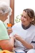 Pflegerin überreicht Patientin einen umschlag