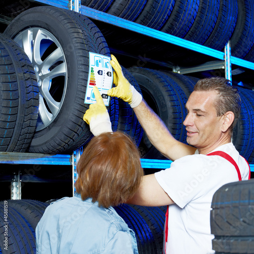 Motor mechanic explains tire labeling to a customer in a garage