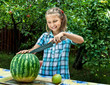 Young girl cut ripe watermelon