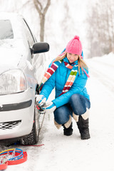 Woman putting winter tire chains car wheel