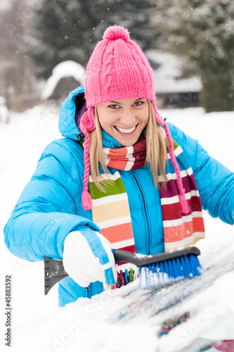 Woman wiping car windshield using brush snow