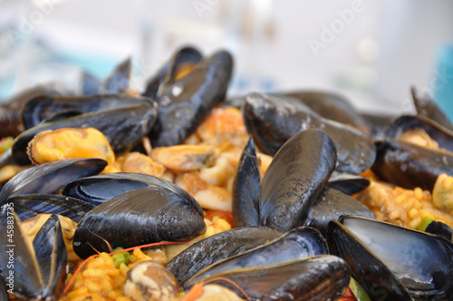 a paella pot with shell fish and rice - 45883735