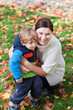 Little toddler boy and young mother in the autumn park