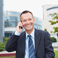 Geschäftsmann telefoniert im Park