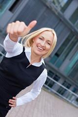 Attraktive Geschäftsfrau hält Daumen hoch