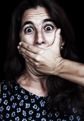 Frightened woman covering her mouth isolated on black