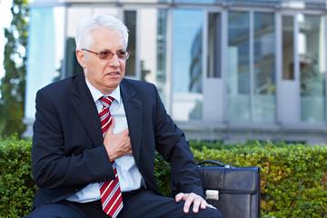 Senior hält sich schmerzende Brust