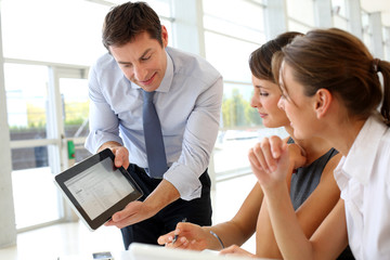 Manager presenting business plan with electronic tablet