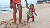 Beautiful mother with baby walking on beach