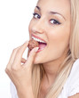 Happy woman eating praline, studio shot