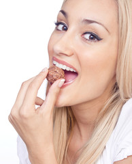 Happy woman eating praline, studio shot