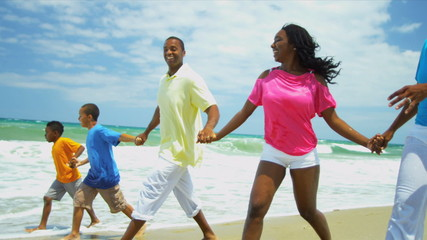 African American family laughing and running together in surfs