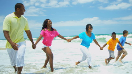 Ethnic family holding hands enjoying running in ocean surfs
