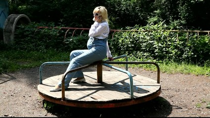 Беременная девушках катается на каруселях в старом парке