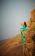 Girl sitting on the edge of a cliff.