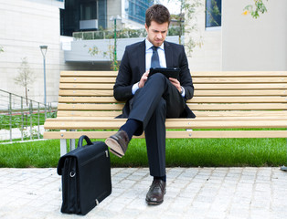 Businessman using a tablet sitting on a bench