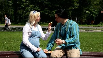 Мужчина и беременная женщина едят пончики