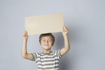 Kind hält ein Werbeschild hoch