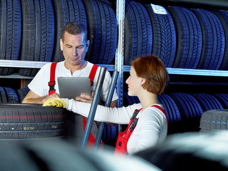 Car mechanics work in a warehouse for tires with touchpad