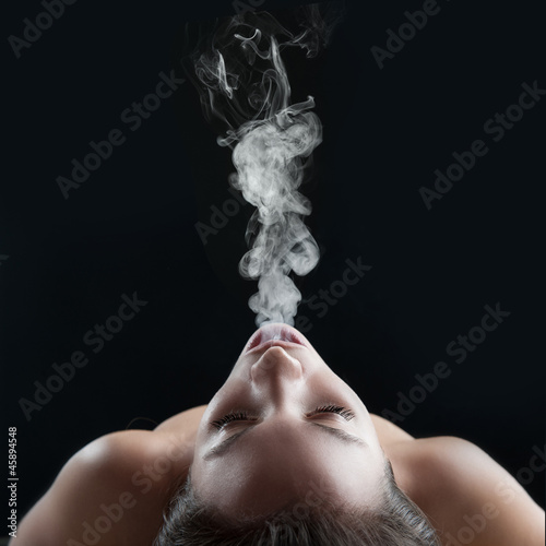 Woman smoking against dark background. Studio fashion photo.