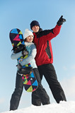 Happy sportswoman and sportsman with snowboard
