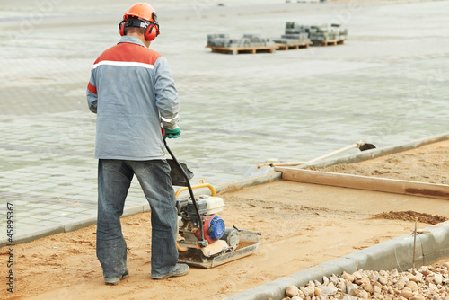 concrete worker work with compactor
