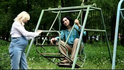 Мужина и беременная женщина отдыхают на детских качелях