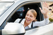 woman sitting in the car and waving her hand