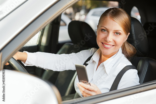woman sitting in the car and holding mobile phone