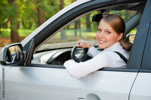 young woman driving the car and smiling