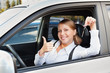 woman holding car key and showing thumbs up