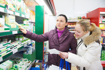 Two women at supermarket dairy shopping