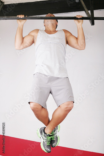 Closeup of young strong teenage athlete doing pull-up on horizon