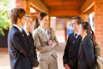 high school teacher talking to students in corridor