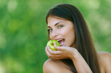 funny young woman bites off an green apple
