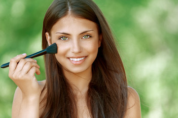 young woman treats her face with brush