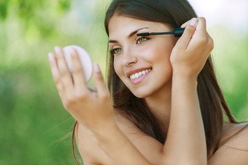 dark-haired smiling young woman dyes her eyelashes