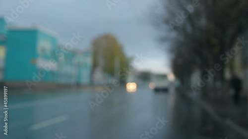 defocused cars moving on street at rain