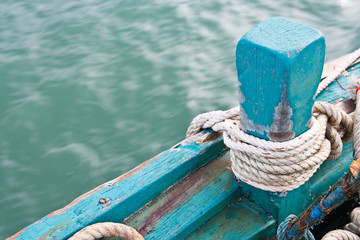 mooring rope tied around green wood anchor
