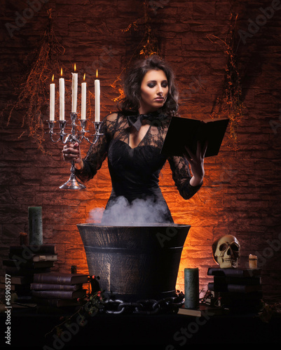 A sexy brunette witch making a mystical poison in a pot