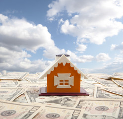 Model of a house with ten dollars on the background