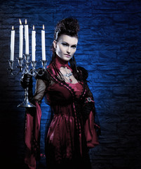 Halloween concept: young and sexy lady vampire holding candles