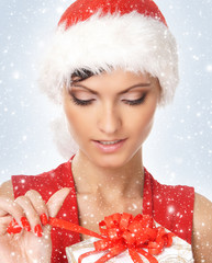 Portrait of a young woman in a Santa hat opening a present