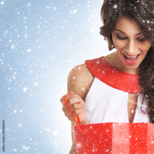 A young brunette woman holding a red shopping bag