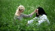 Беременная женщина и мужчина сидят в траве