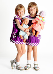 sisters twins in dresses with dolls in studio