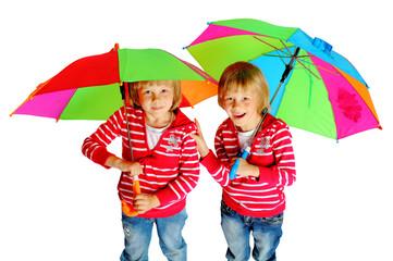 twins stand under multi-colored umbrellas