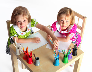 sisters draw at the table color pencils