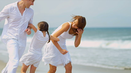Caucasian parents having fun  together young daughter on beach